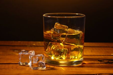 glass of whiskey and ice on wooden table on brown background photo