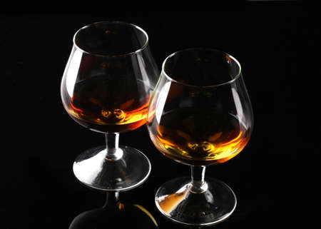 Two glasses of cognac on black background photo