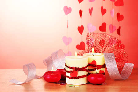 candles for Valentine's Day on wooden table on red background Stock Photo - 12439391