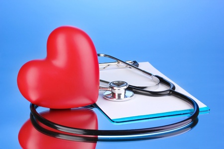 Medical stethoscope with clipboard and heart on blue background photo