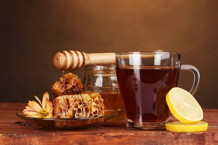 honey, lemon, honeycomb and a cup of tea on wooden table on brown background photo