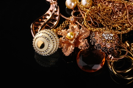 Various gold jewellery on black photo