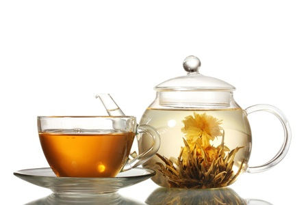 drinking tea: exotic green tea with flowers in glass teapot and cup isolated on white Stock Photo