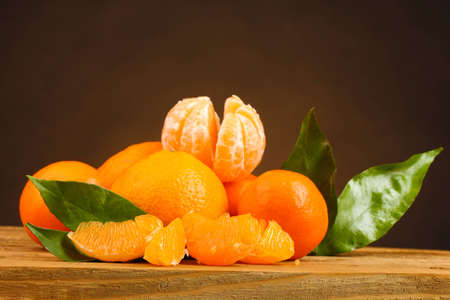 tangerines with leaves on wooden table on brown background photo