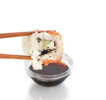 Dipping roll in sauce isolated on white photo