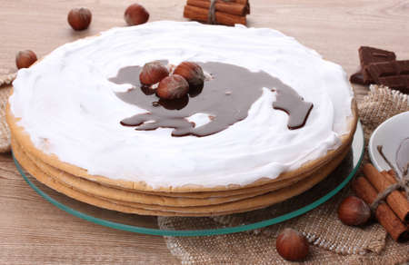 cake on glass stand and nuts on wooden  table photo
