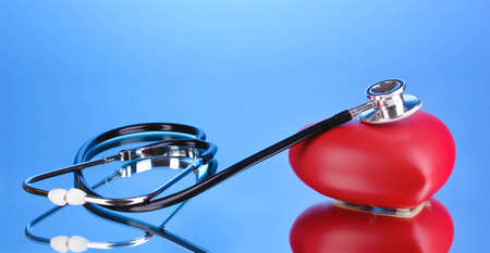 Medical stethoscope and heart on blue background Stock Photo - 12439105