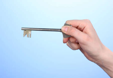 Key in hand on blue background photo