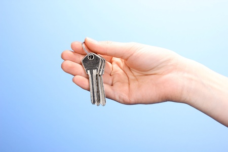 Keys in hand on blue background Stock Photo - 12439059