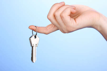 Keys in hand on blue background photo