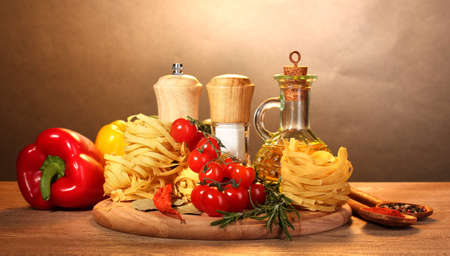 noodles in bowl, jar of oil, spices and vegetables on wooden table on brown background Stock Photo - 12564376
