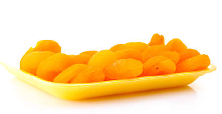 delicious dried apricots in packaging isolated on white photo