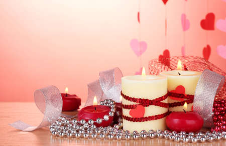candles for Valentine's Day on wooden table on red background Stock Photo - 12564381