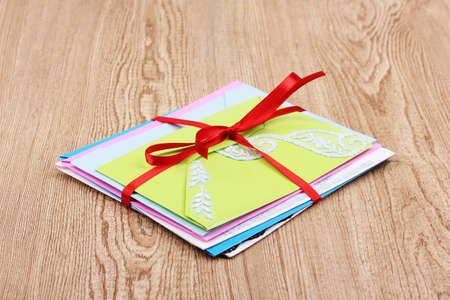 Bunch of color envelopes with ribbon on wooden background photo