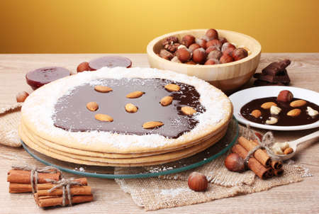 cake on glass stand and nuts on wooden  table on yellow background Stock Photo - 12564353