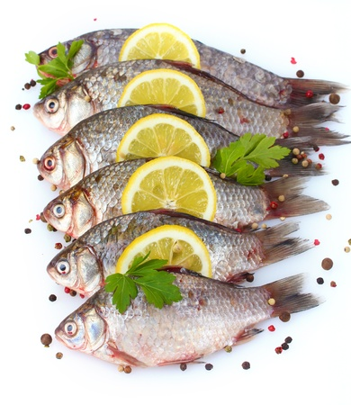 Fresh fishes with lemon, parsley and spice isolated on white Stock Photo - 12564373