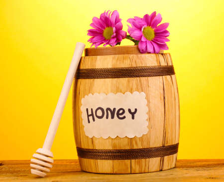 Sweet honey in barrel with drizzler on wooden table on yellow background photo