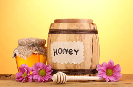 Sweet honey in barrel and jar with drizzler on wooden table on yellow background photo