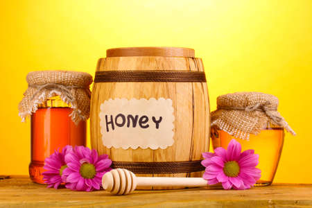 Sweet honey in barrel and jars with drizzler on wooden table on yellow background photo