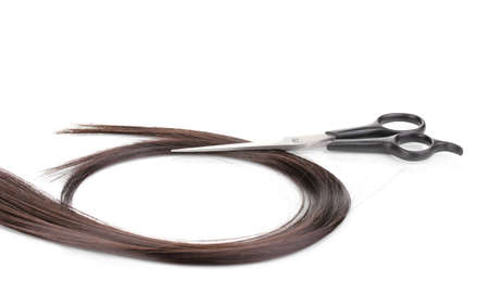 Shiny brown hair and hair cutting shears isolated on white Stock Photo - 12564525