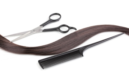 Shiny brown hair with hair cutting shears and comb isolated on white photo
