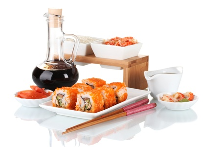 delicious sushi on plate, chopsticks, soy sauce, fish and shrimps isolated on white photo