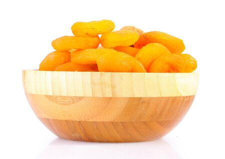 delicious dried apricots in wooden bowl isolated on white photo
