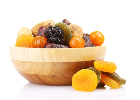 Dried fruits in wooden bowl isolated on white photo