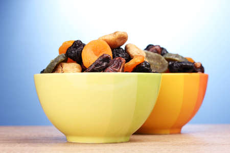 Dried fruits in bright bowls on wooden table on blue background photo