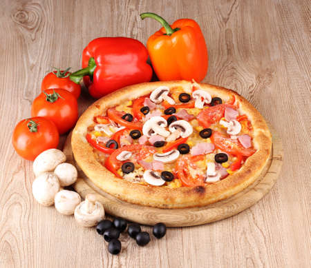 Aromatic pizza with vegetables and mushrooms on wooden background photo