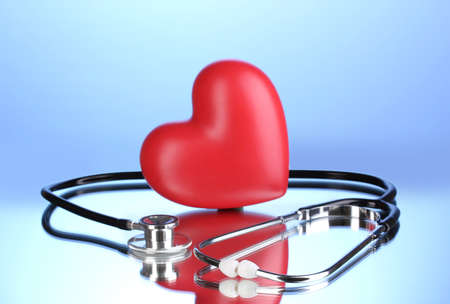 Medical stethoscope and heart on blue background Stock Photo - 12564070