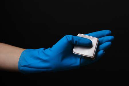Uranium in hand isolated on black photo