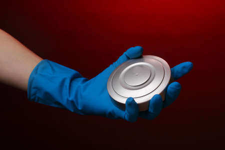 uranium radioactivity: Uranium in hand on red background