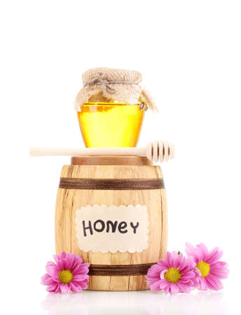 Sweet honey in barrel and jar with drizzler isolated on white photo