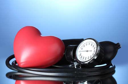 Black tonometer and heart on blue background Stock Photo - 12564068