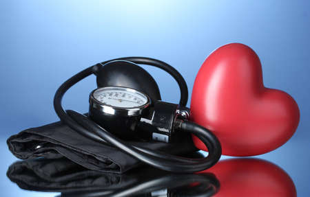 blood supply: Black tonometer and heart on blue background Stock Photo