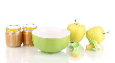 Jars of baby puree with plate, spoon and apples isolated on white photo