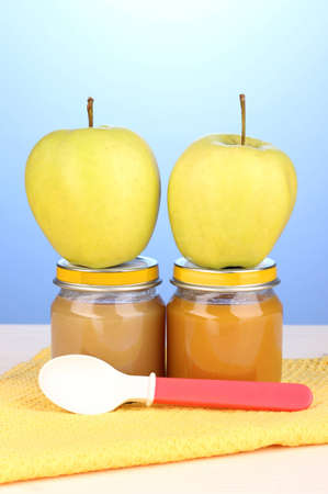 Jars of baby puree with spoon on napkin on blue background photo