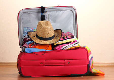 Open red suitcase with clothing in the room Stock Photo - 12665772