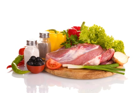 Raw meat and vegetables on a wooden board isolated on whitе photo