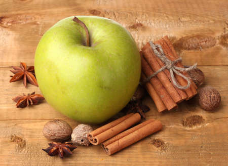 Cinnamon sticks, green apple, nutmeg,and anise on wooden table photo