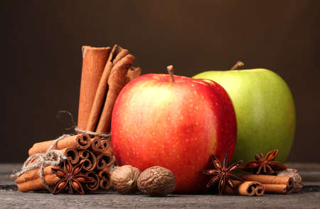 Cinnamon sticks,apples nutmeg and anise on wooden table on brown background photo