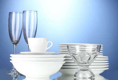 empty bowls, plates, cups and glasses on blue background Stock Photo - 12664560