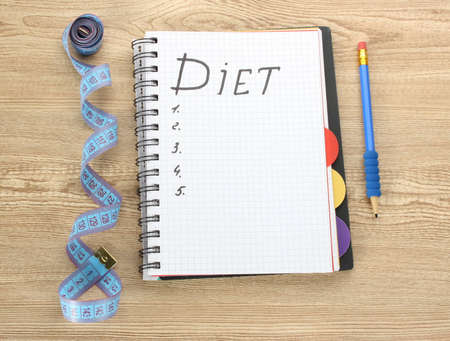 Planning of diet. Notebook measuring tape and pen on wooden table Stock Photo - 12664705