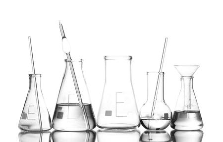 probeta: Cristalería de laboratorio diferente con el agua y el vacío con la reflexión aislada en blanco