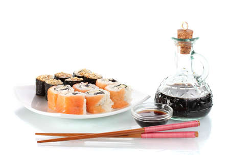 Tasty rolls served on white plate with chopsticks and soy sauce isolated on white photo