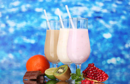 Milk shakes with fruits and chocolate on blue background photo