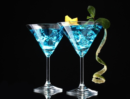 Blue cocktail in martini glasses on black background photo