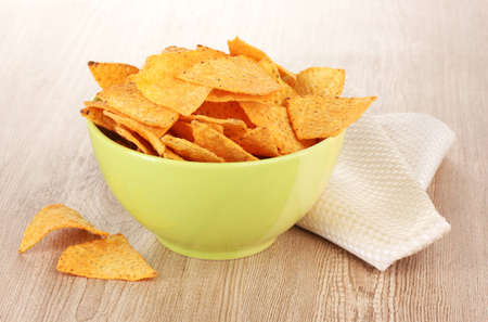 tasty potato chips in green  bowl on wooden table Stock Photo - 12664908