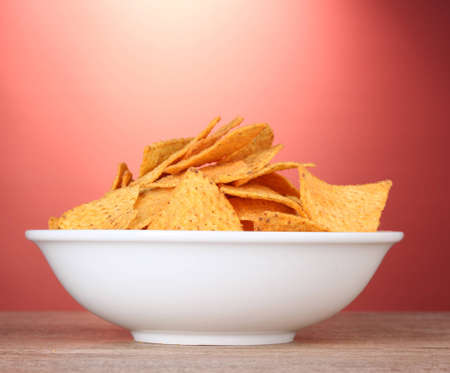 tasty potato chips in white  bowl on wooden table on red background Stock Photo - 12664423